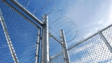 image of barbed wire atop chain link fence at a prison