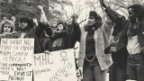 "In this black and white photo, five students in front of a group stand holding hands over their heads. Two signs read ""Mount Holyoke [women] oppose apartheid"" and ""We want no part of profits from South Africa! Our community votes no! MHC divest now!"""