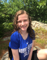 Kiely Quinn, wearing a blue Mount Holyoke t-shirt, sitting on rocks with greenery as the background.