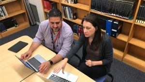 Mount Holyoke's Ruth Hornsby, assistant director of grad programs, and Julio Hernandez, a grad student in the teaching program, sit at tables and work together on their laptops.
