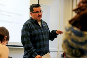David Hernandez in a blue check shirt, standing in front of undergraduates, discussing a topic