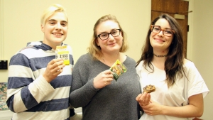 Three students enjoying milk and cookies
