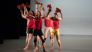 Five dancers on a stage in red tops holding roses in each hand and in their mouths.