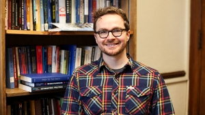 This is a portrait of Adam Hilton, assistant professor of politics, standing in front of a bookcase. He is wearing a plaid shirt and glasses, smiling.