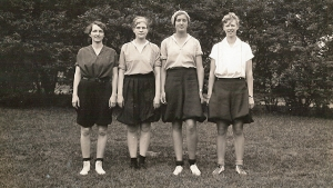 This is an 1933 photograph of four Mount Holyoke athletes in bloomers and short-sleeved blouses.
