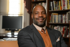 Jelani Cobb in his study, smiling at the camera and surrounded by books and a computer screen.