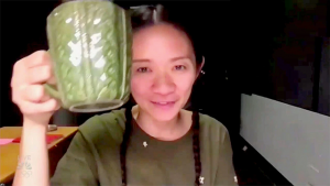 This is a photograph of Chloe Zhao raising her green mug to accept her Golden Globe at the ceremony which was held over Zoom.