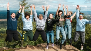 Students leap into the air at the top of the mountain.