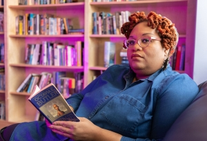 Dr. Susana Morris '02 reading a book, in front of bookshelves