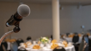 This is a photograph of a microphone, with an out-of-focus banquet room in the background.