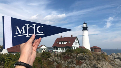 MHC flag in front of a seaside building with a lighthouse