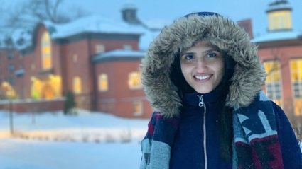 Ammal Abbasi on the wintery Mount Holyoke campus with a snow jacket and fuzzy hood.
