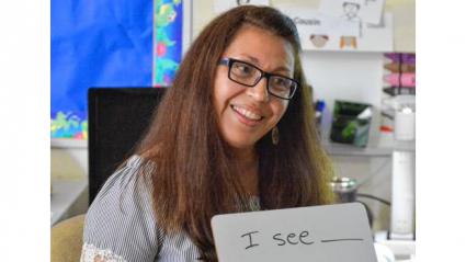 """Blanca Osario-Castilo, holding up a whiteboard with the words """"I see ___, I think ___."""" on it."""
