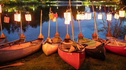 Canoes with lanterns lined up on the shore of the lake at twilight in advance of Canoe Sing.