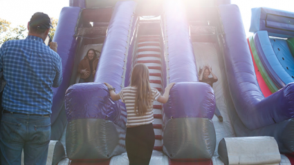 People stand at bottom of bouncy slide with the sun behind it.