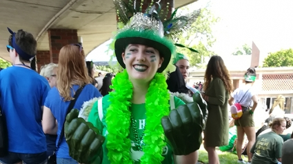 Junior Grace Alexander grins at the camera. She is decked out in a green top hat, lei, shirt and boxing gloves.