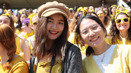 Incoming students in yellow grin under the sun at Convocation 2019.