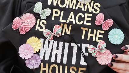 "This is a close-up shot of a decorated mortarboard that reads, ""A woman's place is in the White House."""