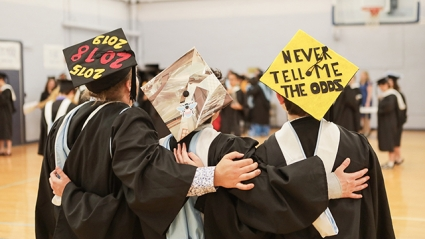 "This is a picture of the back of three graduates wearing decorated mortarboards. The left one reads, ""2019."" The center one is decorated with a bee in pink, light blue and white. The one on the right reads ""Never tell me the odds."""