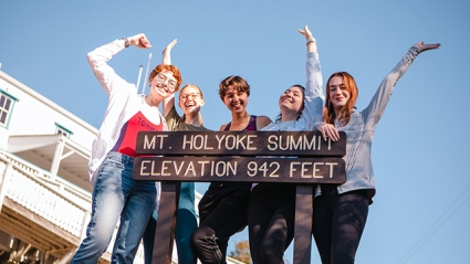 """This is a photograph of students posing at the top of the mountain by a sign that reads, """"Mt. Holyoke Summit, Elevation 942 Feet."""""""