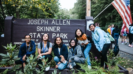 This is a photograph of students posing in front of a park sign for Joseph Allen Skinner State Park, where the hike up the mountain begins.