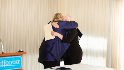 two women hugging at an awards ceremony