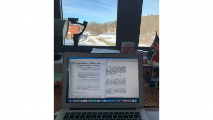 A laptop open with readings displayed on the screen; above the laptop a window looks out over a lake