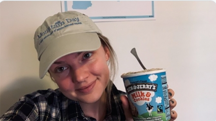 A student smiling into the camera wearing a Mountain Day baseball cap holding a pint of Milk & Cookies ice cream
