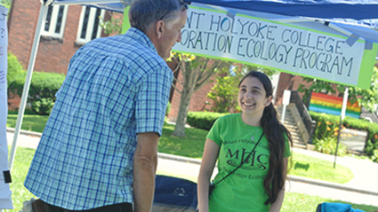 Photo of a restoration ecology student discussing the program at the South Hadley Farmers Market