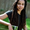 Suzan Lori Parks sitting on a bench slightly smiling