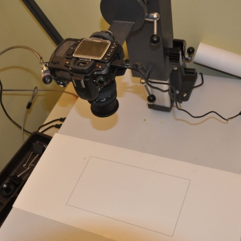 A DSLR camera mounted in a copy stand and pointed at a white sheet of paper with a rectangle outlined on it.