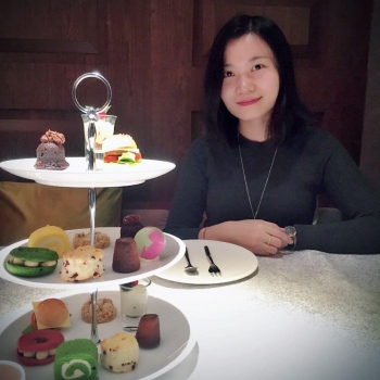 Zhang Yang next to a tray of macaroons.