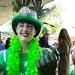 Junior Grace Alexander grins at the camera. She is decked out in a green top hat adorned with shining feathers and accents, a green lei, and green shirt to denote her class affiliation.