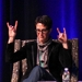 """Rachel Maddow sitting onstage in conversation, making the """"rock on,"""" gesture with both hands,"""