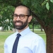 Ali Aslam, assistant professor of politics, smiling, standing in front of a tree on the Mount Holyoke College campus.